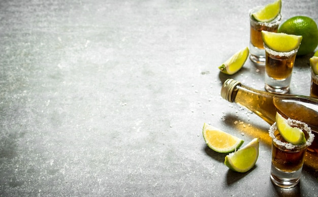 ライムと塩のテキーラのボトル。石のテーブルの上。