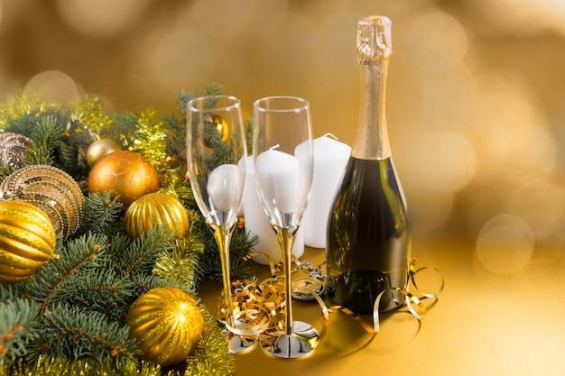 ラベルのない封印されたクリスマスシャンパンのボトルは、コピースペースで背景がぼやけた金のつまらないもので飾られた松の枝と一緒に2つのスタイリッシュなフルートで立っている季節を祝います