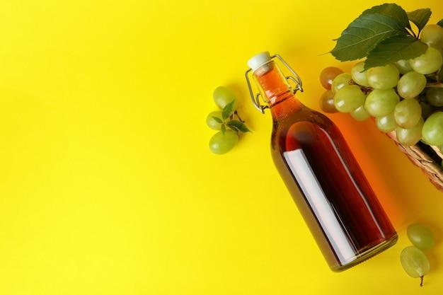 酢のボトルと黄色の背景にブドウとバスケット