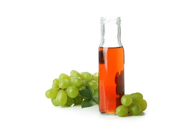 白い背景で隔離の酢とブドウのボトル