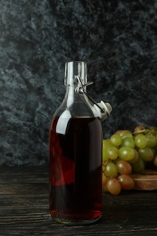 素朴な木製のテーブルに酢とブドウのボトル