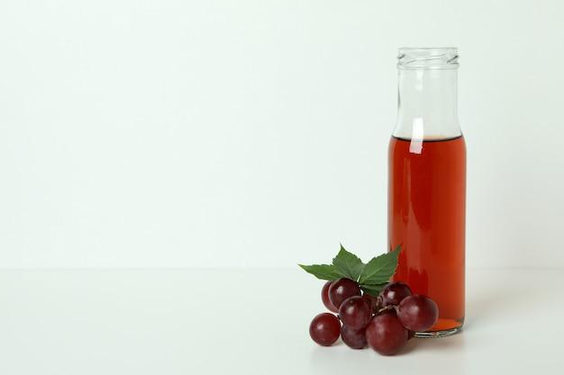 白いテーブルの上の酢とブドウのボトル