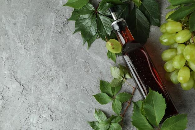 灰色のテクスチャテーブルに酢、ブドウ、葉のボトル