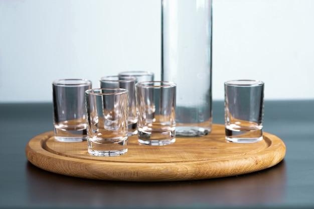Бутылка водки и крупным планом рюмки.