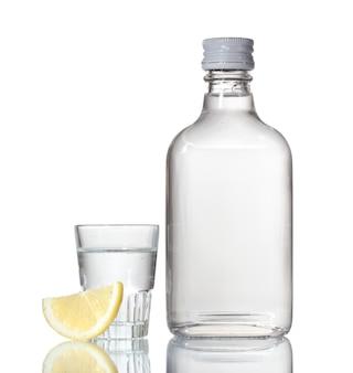 Бутылка водки и рюмки с лимоном, изолированные на белом