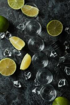 Бутылка водки, рюмки, кубики льда и ломтики лайма на черном дымчатом столе
