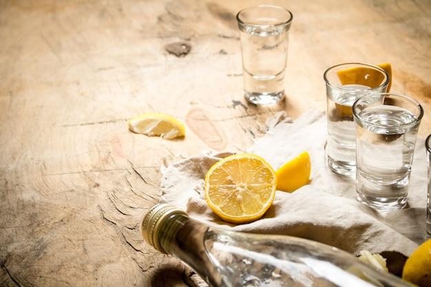 유리 잔과 레몬 보드카 병입니다. 나무 배경.