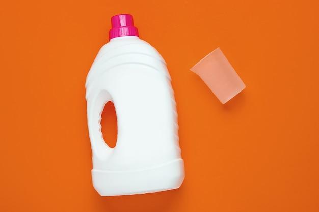 洗浄ゲルのボトル、オレンジ色の背景に空の測定容器。上面図