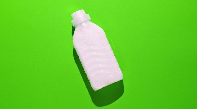 Бутылка геля для стирки на зеленом.