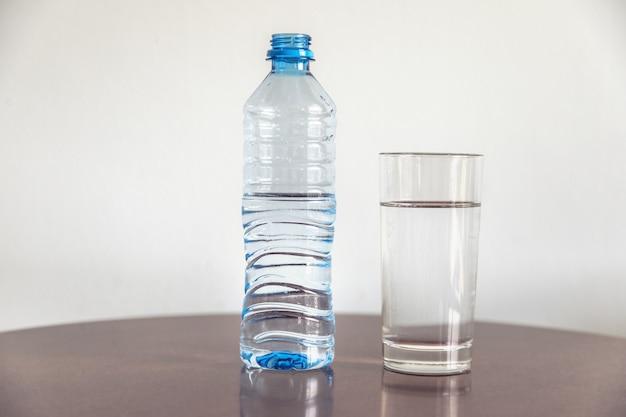 Бутылка воды и стакан на столе