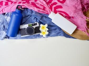 水のボトル、フィルムカメラ、白プルメリアの花の敷物、白いボトルの色をモックアップ