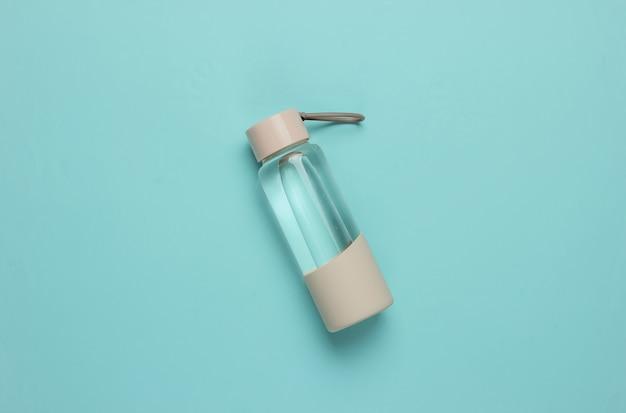 青い背景の上のスポーツや野外活動のための水のボトル。上面図