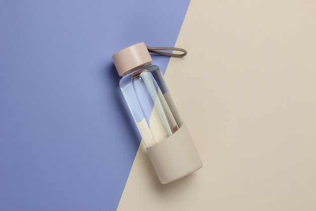 色付きの背景にスポーツや野外活動のための水のボトル。上面図