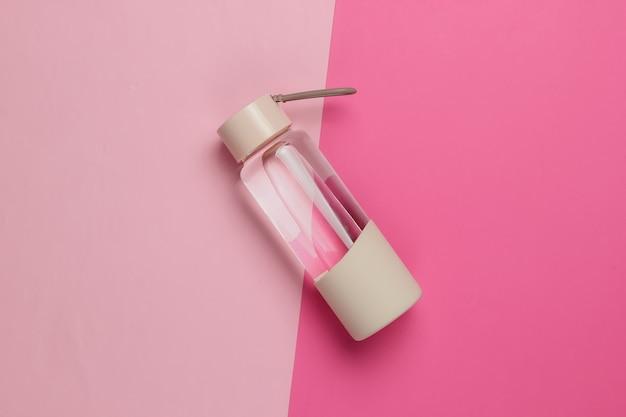ピンクのパステルカラーの背景にスポーツやアウトドアアクティビティ用の水のボトル。上面図