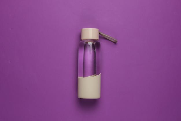 紫色の背景にスポーツや野外活動のための水のボトル。上面図