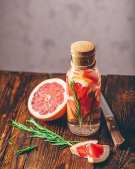 スライスした生のグレープフルーツとローズマリーの新鮮な温泉を注入した水のボトル。垂直方向。