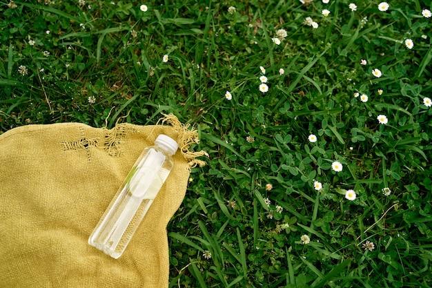물 한 병은 데이지 사이에서 푸른 잔디에 담요에 놓여 있습니다.