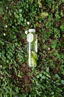 물 한 병은 데이지 사이에서 푸른 잔디에 놓여 있습니다.