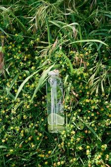 물 한 병은 야생화 중 푸른 키 큰 잔디에 놓여 있습니다.