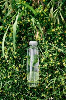 물 한 병은 노란색 야생화 중 푸른 키 큰 잔디에 놓여 있습니다.