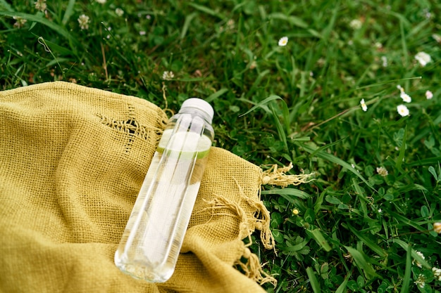 레몬 조각과 물 한 병은 녹색 초원에 침대보에 놓여 있습니다
