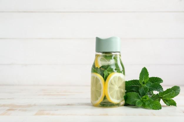 Бутылка воды со свежим лимоном и мятой на светлом фоне
