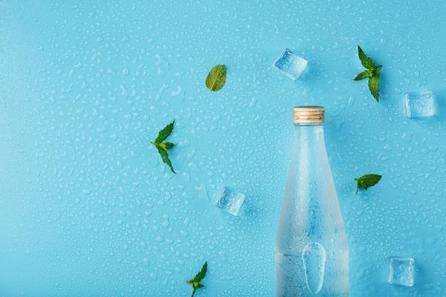 アイスキューブとミントの葉と水のボトル