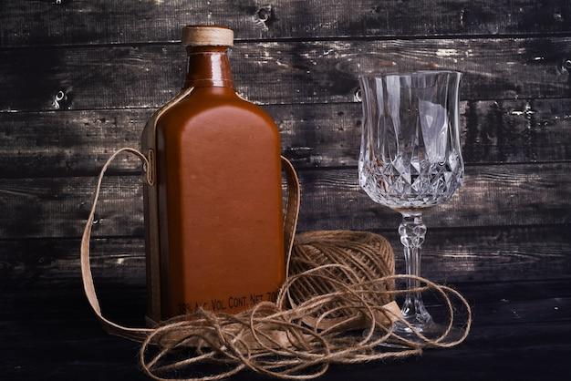 ウイスキーと黒い木製の空のワイングラスのボトル
