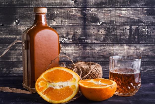 위스키와 유리 및 잘 익은 오렌지의 병. 위스키 한 잔.