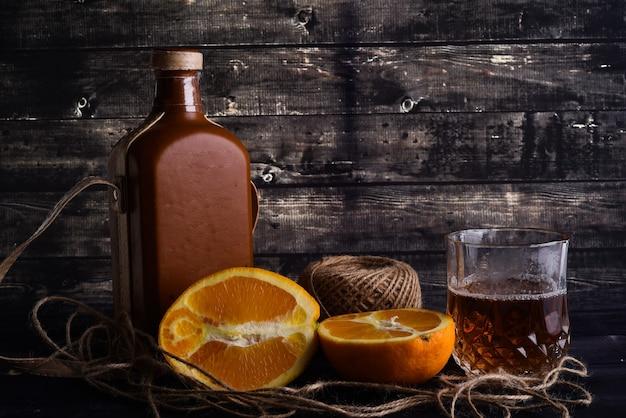 위스키와 유리 및 어두운 나무 배경에 잘 익은 오렌지의 병. 위스키 한 잔.