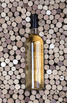 Бутылка белого вина и пробки на деревянном столе