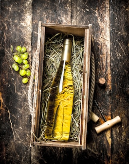 古い箱に入った白ワインのボトル。木製の背景に。