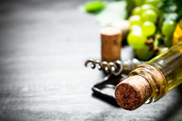 黒の木製の背景にコルク栓抜きと白ワインのボトル