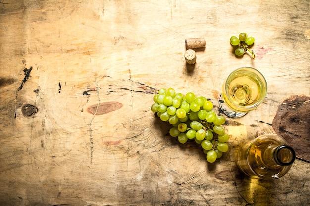 코르크와 화이트 와인 한 병입니다. 나무 배경.