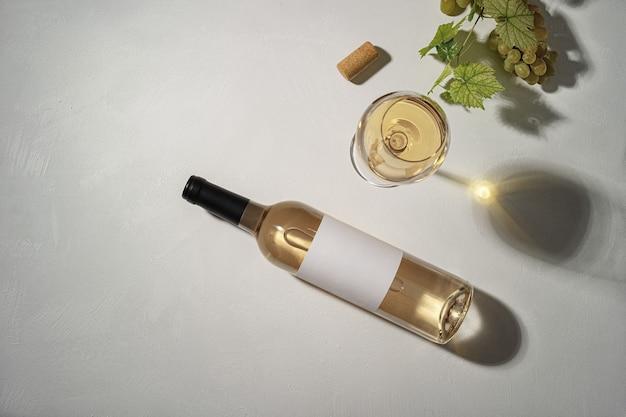 Бутылка белого вина с этикеткой. бокал вина и винограда. макет бутылки вина. вид сверху.