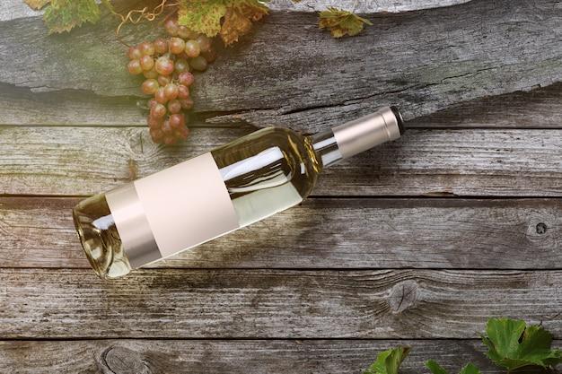 ラベル付きの白ワインのボトル。グラスワインとブドウ。ワインボトルのモックアップ。上面図。