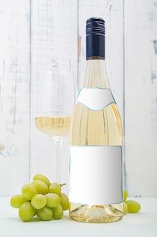 레이블이있는 화이트 와인 한 병입니다. 와인과 포도의 유리. 와인 병 모형.