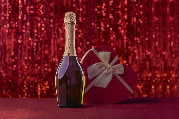 빨간색 빛나는 표면에 활이 달린 하트 모양의 와인과 선물 상자