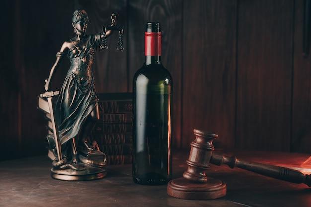 木製のテーブルの上の法の象徴としてのワインのボトルと正義の女性と裁判官のガベル