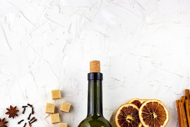 白い背景の上のワインとスパイスのボトル。グリューワインの材料。シナモン、アニススター、オレンジ、ブラウンシュガー、クローブ。クリスマスの温かい飲み物
