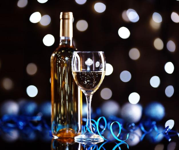 Бутылка вина и бокал с рождественским украшением на ярком фоне
