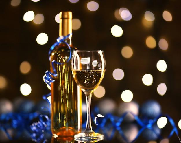 明るい表面にクリスマスの装飾が施されたワインとワイングラスのボトル