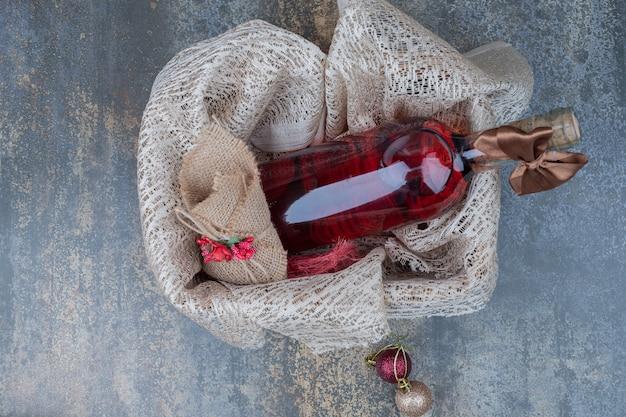 나무 바구니에 리본으로 장식 된 와인 한 병. 고품질 사진