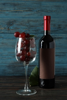 木製のテーブルにワインのボトル、ブドウのグラスと葉
