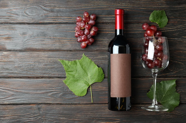 ワインのボトル、ブドウのグラスと木製のテーブルの葉