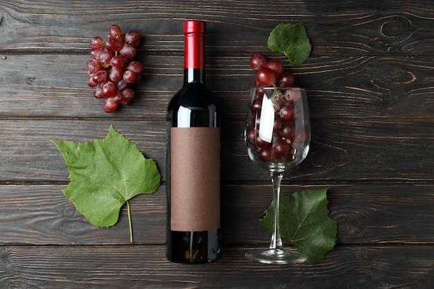 와인 한 병, 포도 한 잔, 나무 탁자에 있는 잎
