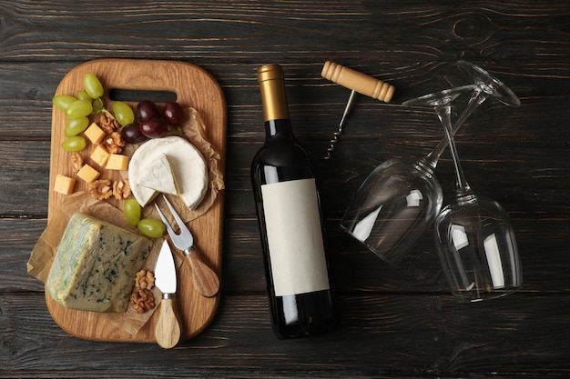 Бутылка вина, бокалы, сыр и фрукты на деревянный