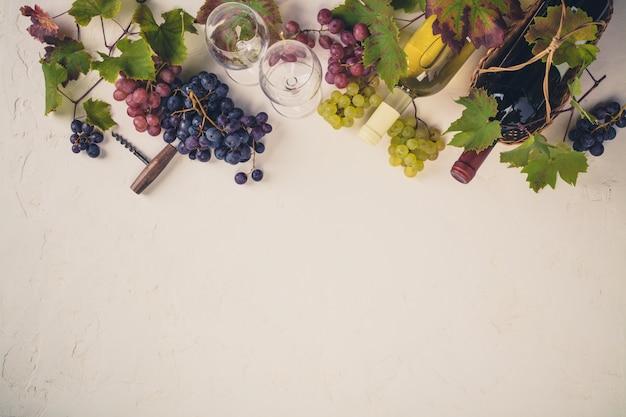 Бутылка вина, бокалы, виноград и виноградные листья на бежевом фоне. вид сверху