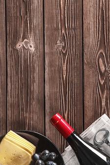 木製の背景にワイン、ブドウ、チーズのボトル。コピースペース。