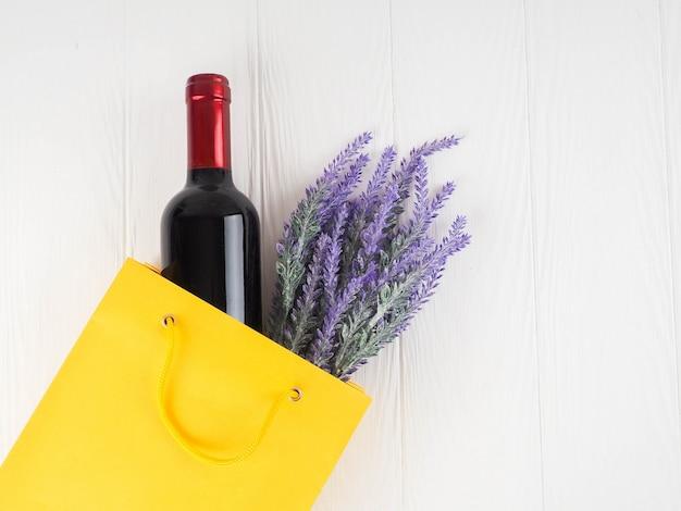 ライラックの花とパッケージのワインのボトル、フラットレイアウト